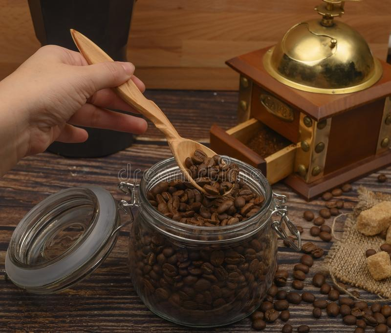 The girl`s hand takes a wooden spoon of coffee beans from a glass jar, a coffee grinder, pieces of brown sugar on a wooden stock photography