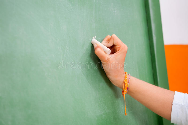 Girl's Hand Writing On Green Chalkboard In stock photo