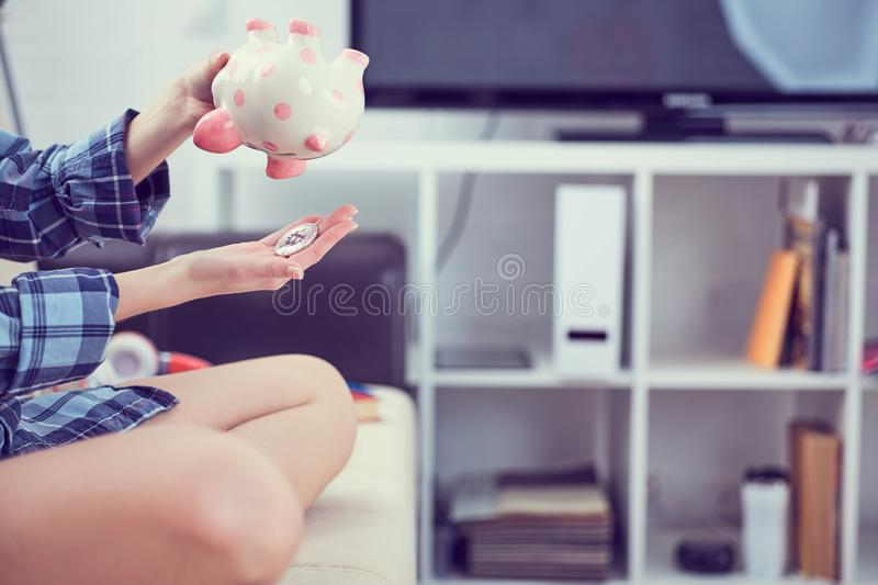 Girl`s hands holding a piggy Bank and pouring bitcoins out of it. Concept of the fall in the value of cryptocurrency. Girl`s hands holding a piggy Bank and stock photo