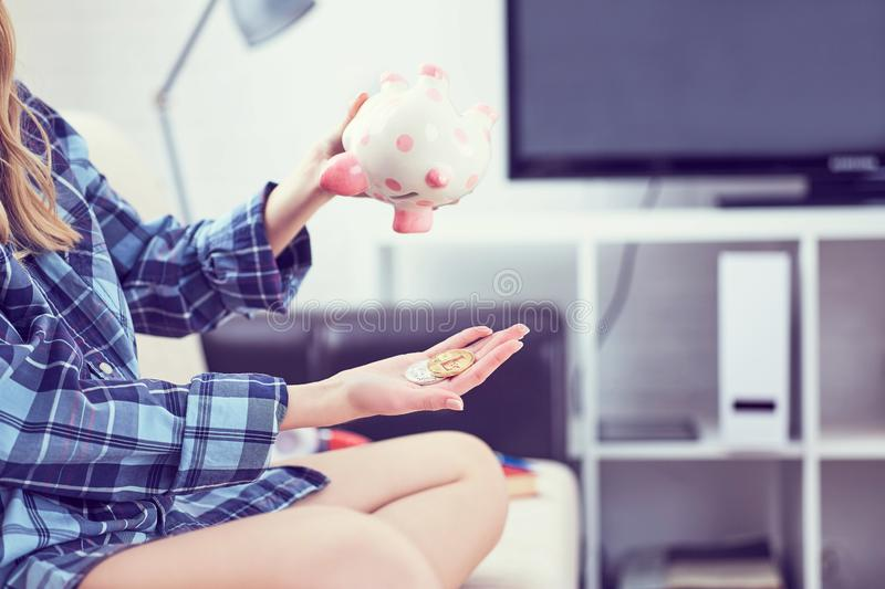 Girl`s hands holding a piggy Bank and pouring bitcoins out of it. Concept of the fall in the value of cryptocurrency. Girl`s hands holding a piggy Bank and royalty free stock photos