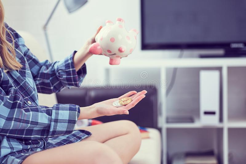 Girl`s hands holding a piggy Bank and pouring bitcoins out of it. Concept of the fall in the value of cryptocurrency. Girl`s hands holding a piggy Bank and royalty free stock image