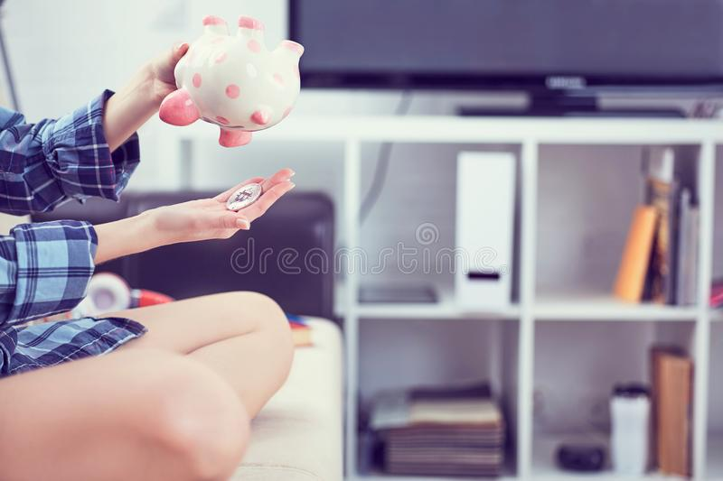 Girl`s hands holding a piggy Bank and pouring bitcoins out of it. Concept of the fall in the value of cryptocurrency. Girl`s hands holding a piggy Bank and stock images