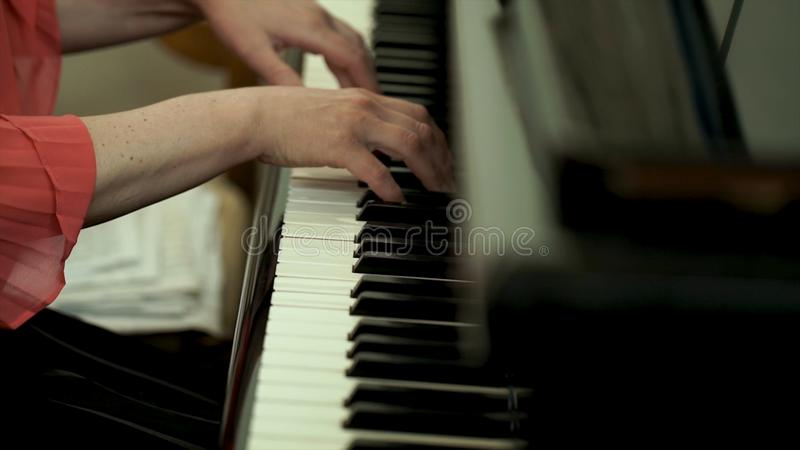 Girl`s hands on the keyboard of the piano. The girl plays piano,close up piano. Hands on the white keys of the Piano stock image