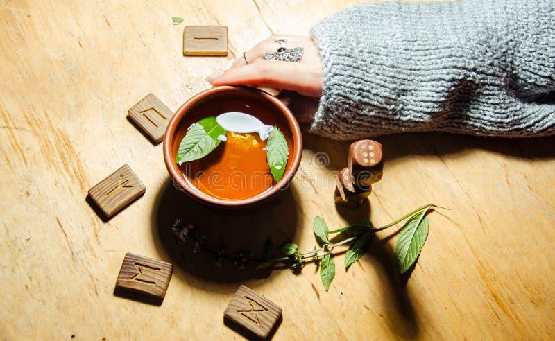 Girl& x27;s hands, runes and hot mint tea stock photography
