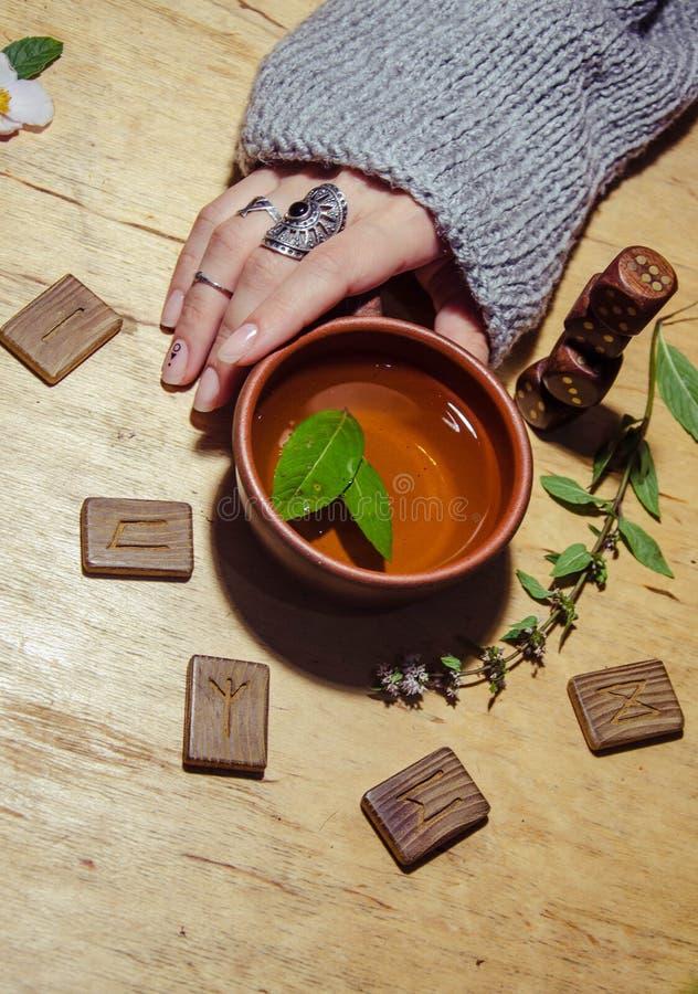 Girl& x27;s hands, runes and hot mint tea stock image