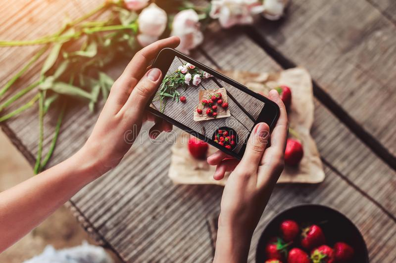 Girl`s hands taking photo of breakfast with strawberries by smartphone. Healthy breakfast, Clean eating, vegan food concept. royalty free stock photo