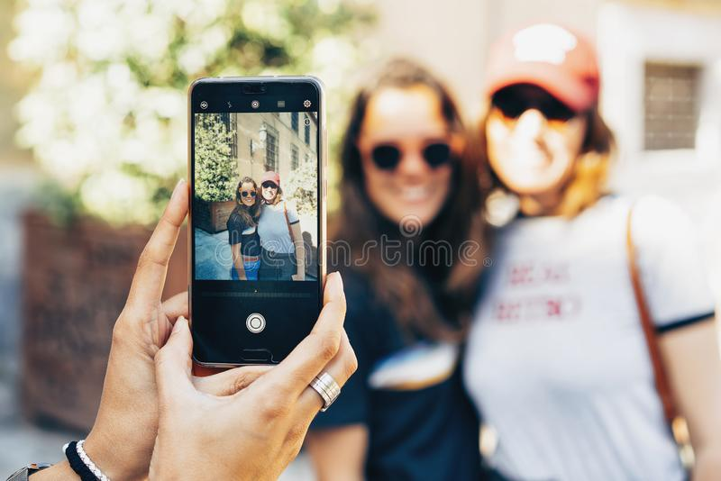 Girl`s hands taking photo with a smartphone of a happy women lesbian couple in Madrid. Same sex relationship and real love concep. T stock photography