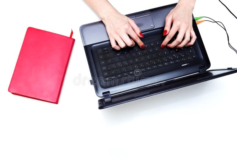 Girl`s hands typing on the keyboard. Workspace with girl`s hands, laptop, pink peony bouquet, golden accessories, mint diary. To stock image