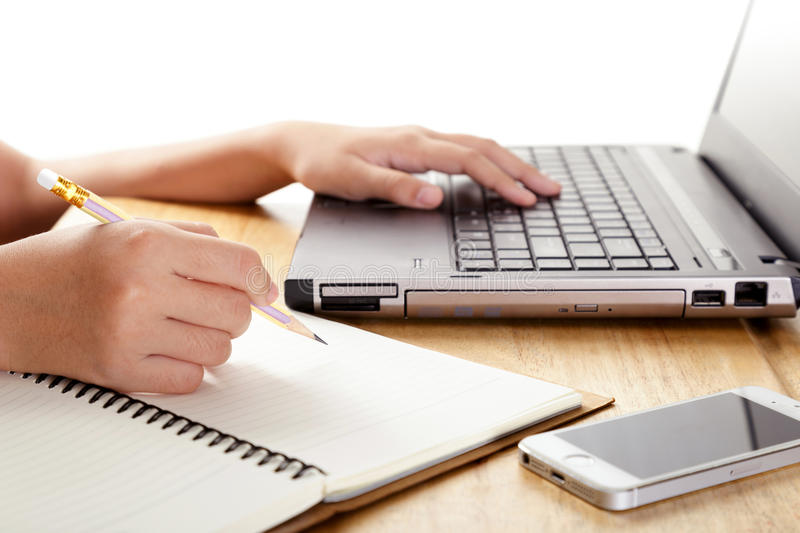 Girl`s hands writing in notebook and using laptop. stock photography