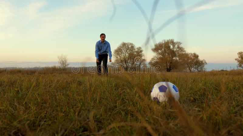Girl`s leg hits soccer ball man catches ball. family plays football in park. dad and daughter play ball on the field. royalty free stock images