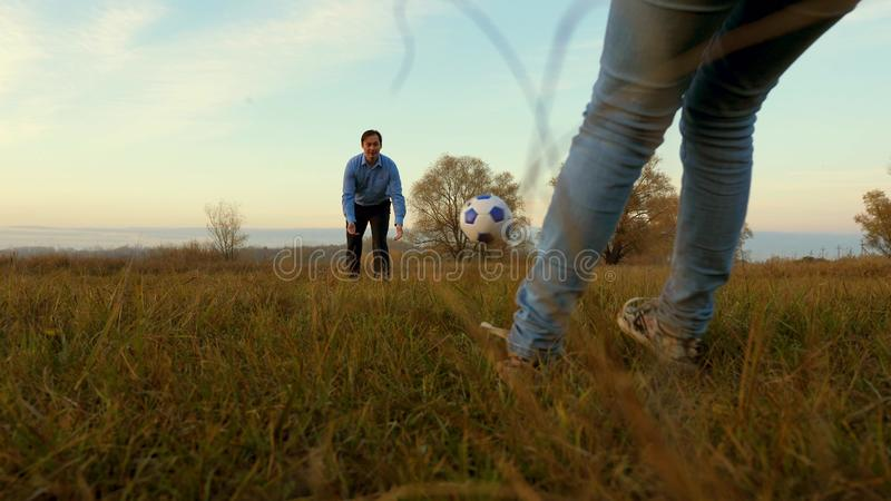 Girl`s leg hits soccer ball man catches ball. family plays football in park. dad and daughter play ball on the field. stock images