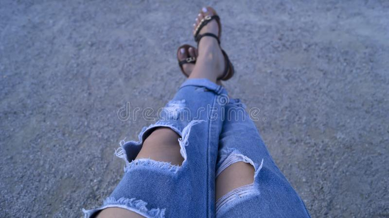 Girl`s legs dressed in ripped blue jeans stock photos