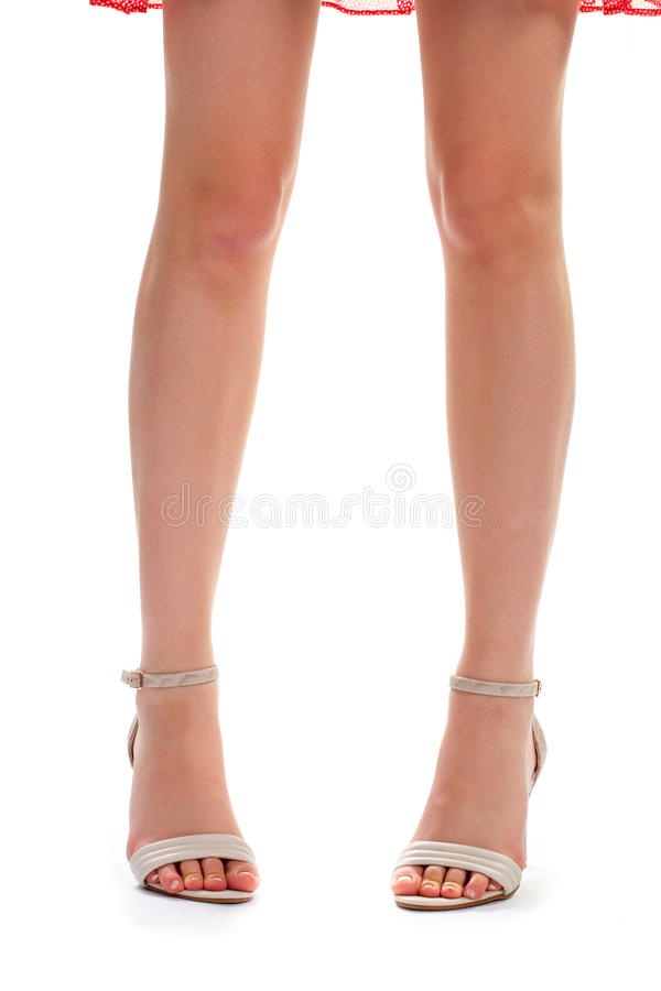 Girl's legs in heel shoes. Front view of beige heels. Exclusive footwear purchased at boutique. Quality and design stock photo