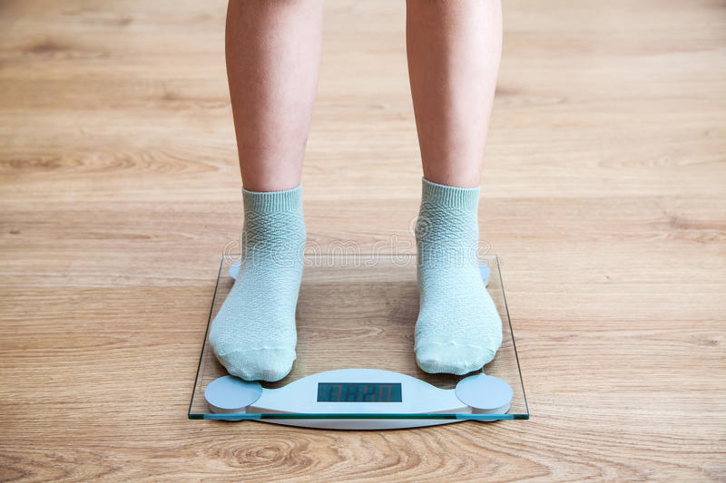 Girl's legs standing on the scales. Girl's legs standing on the glass scales closeup. front view royalty free stock photos