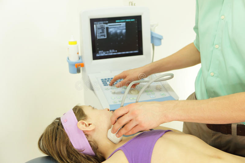 Girl's neck diagnosis with an ultrasound. Girl's neck diagnosis carried out with the use of an ultrasound stock images