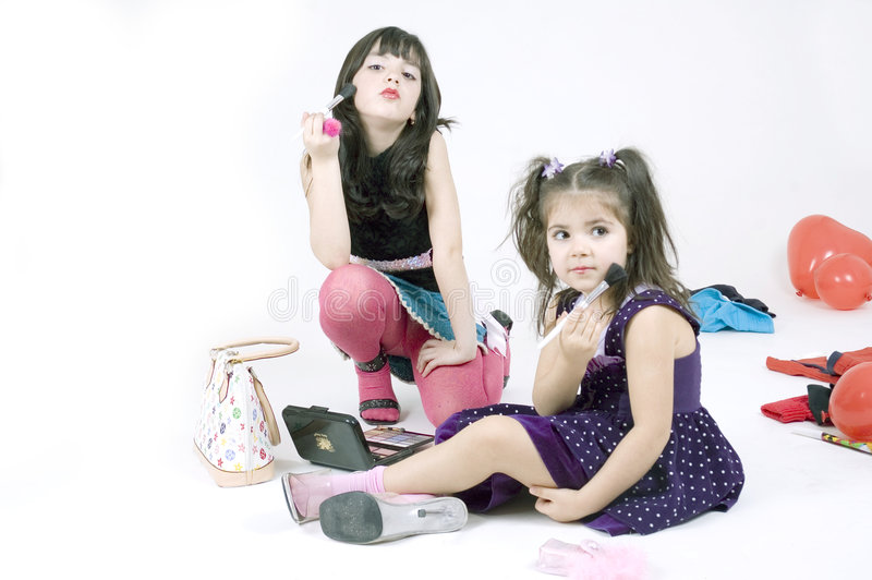Girl's paradise. Two little sisters, a seven and a three year old play with make-up, posing as pop-stars, having fun. Look how sweet they are stock image