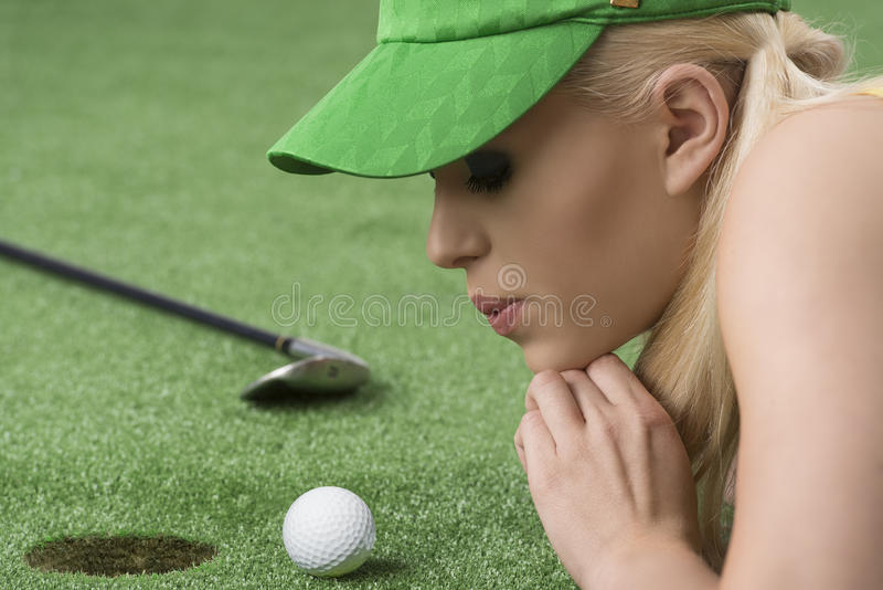 Girl's playing with golf ball, she blows on that royalty free stock image