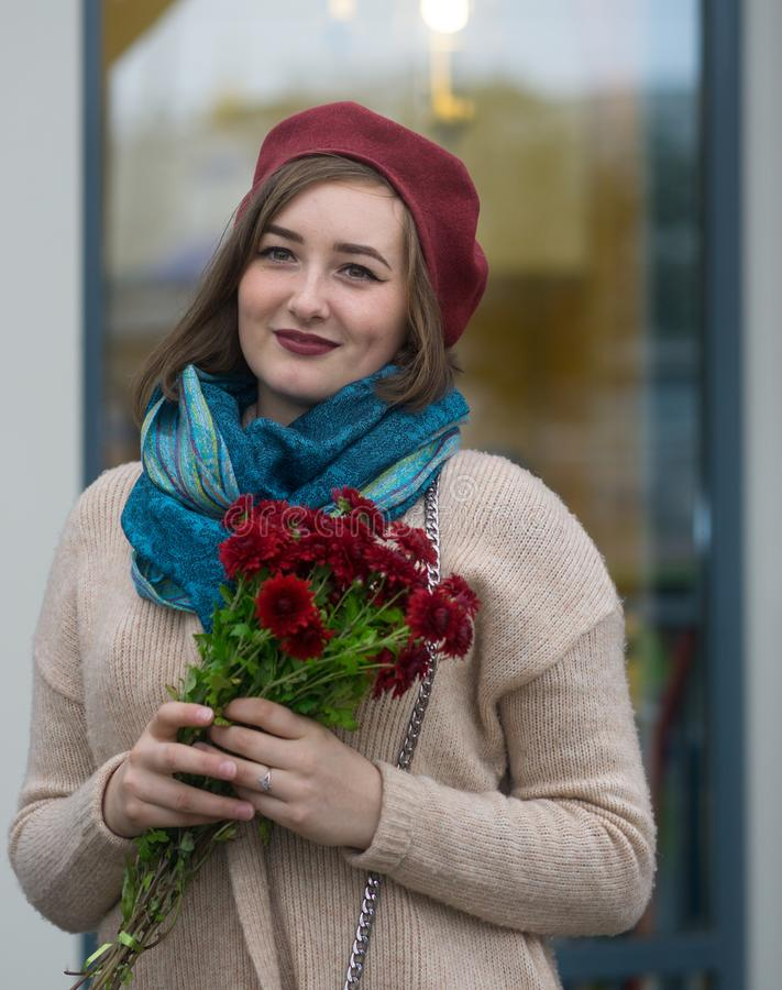 Portrait of the lovely girl with flowers. The girl`s portrait in a red beret, with a bouquet of flowers, in a beige cape. With a blue scarf. She lovely smiles royalty free stock photos