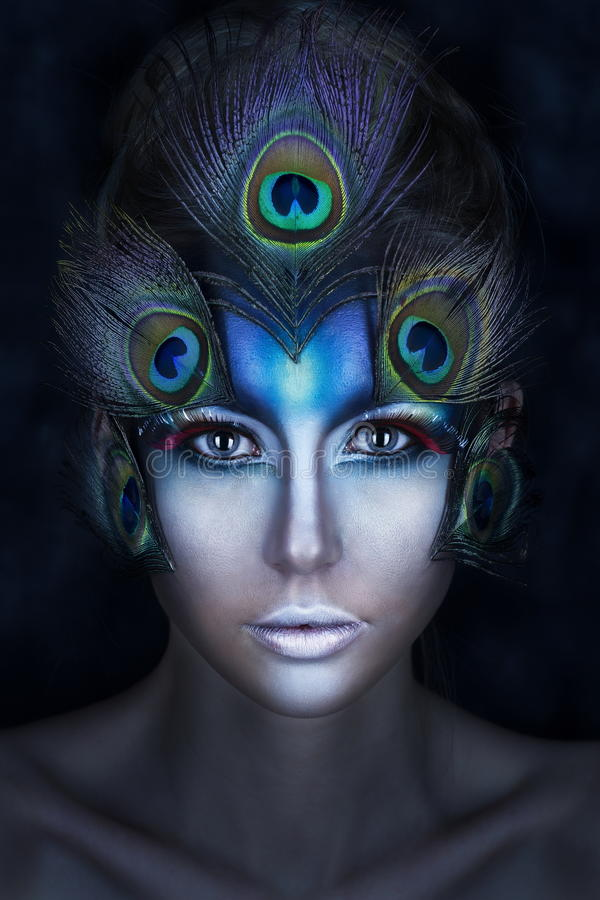 The girl`s portrait with a vanguard make-up and feathers of a peacock in blue tones stock photo
