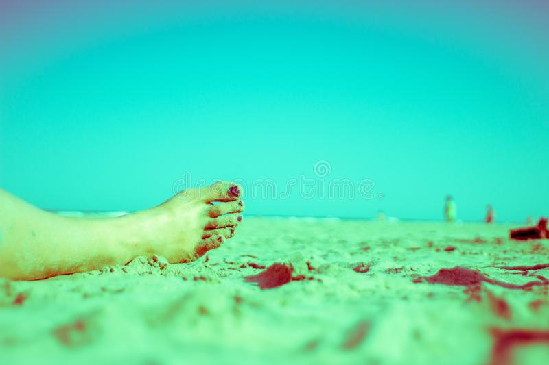 Girl Relaxing on the Beach Stylized Magenta. Girl`s right Leg Relaxing on the Beach magenta stylized stock photography