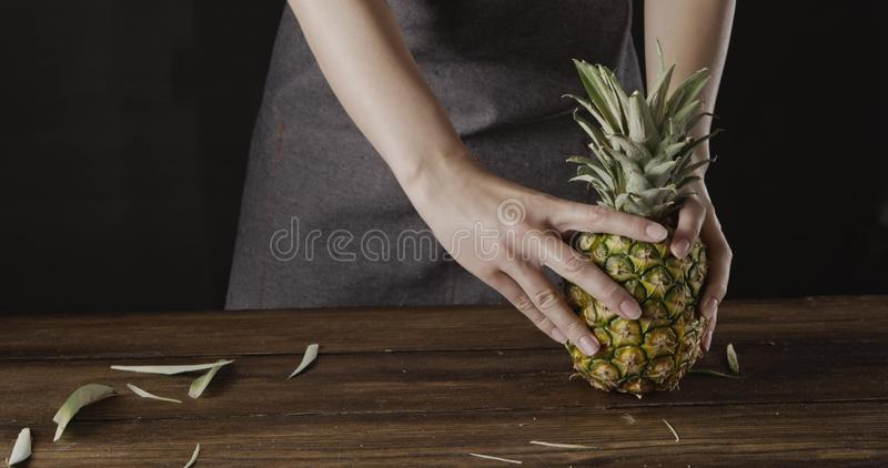 Woman` hands with ripe juicy natural organic tropical fruit pineapple on a wooden kitchen table on a black background. Girl`s in a textile apron holds fresh stock photography