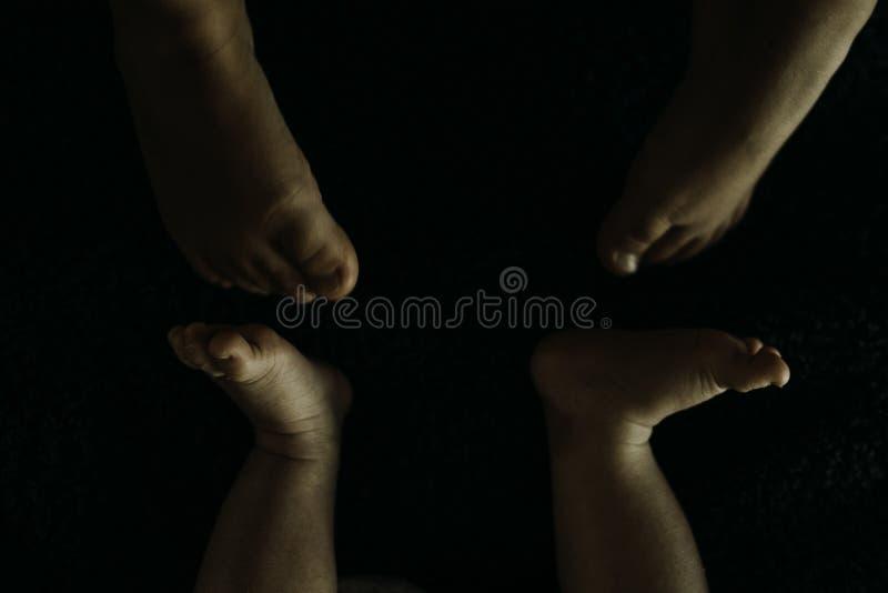 girl& x27; s voeten en baby& x27; s voeten wat betreft stock afbeelding