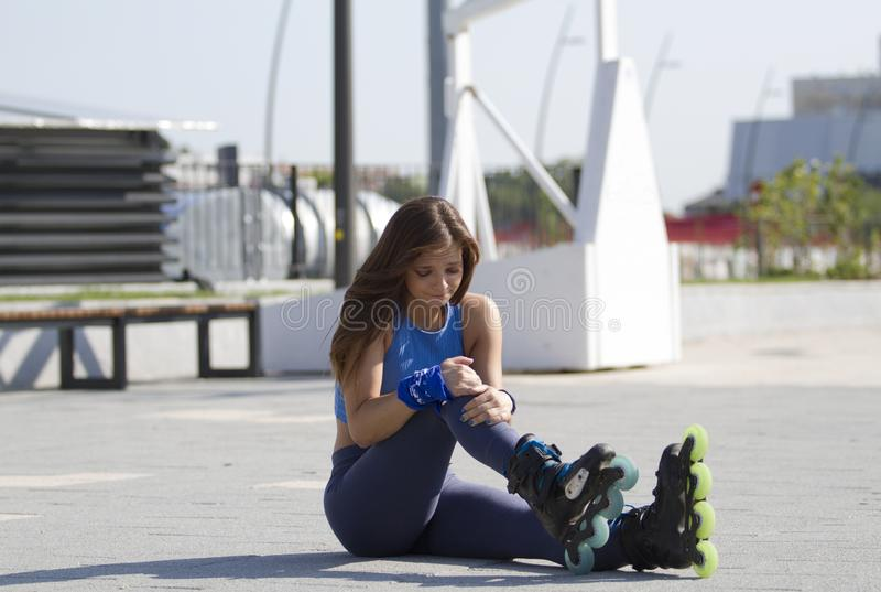 The girl.She is sad and crying in pain. She probably fell while driving, in-line skate. The girl in the blue T-shirt sits on the concrete and holds on to her royalty free stock photos