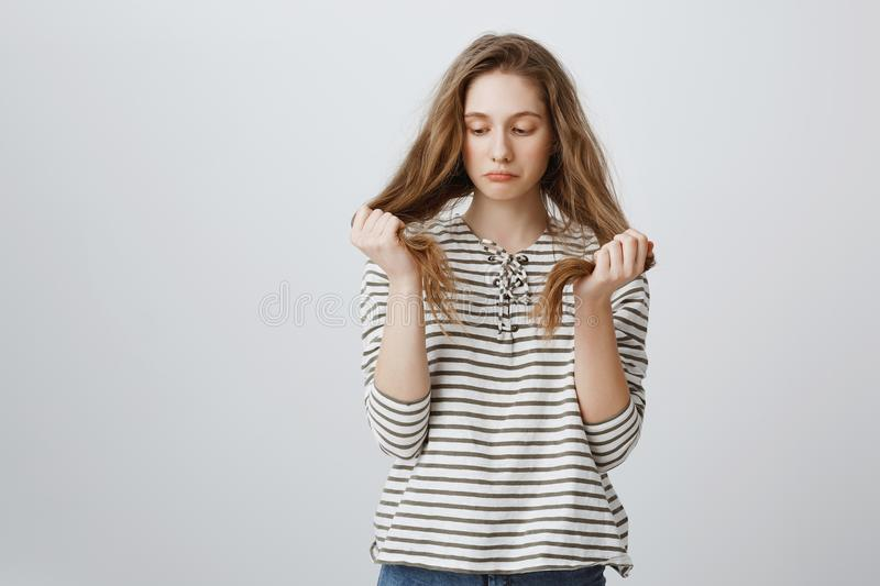 Girl is sad of her bad hair strands. Portrait of gloomy bothered young woman holding hair and being upset, having split royalty free stock photo
