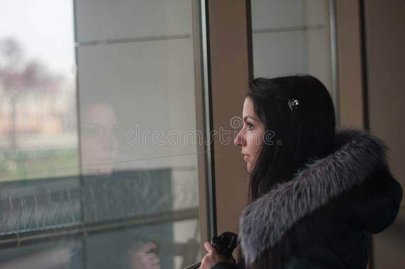 The girl is sad looking out the window. Art portrait of a beautiful young sadly girl looking through the window royalty free stock images
