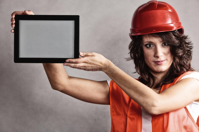 Girl in safety helmet showing tablet. Girl worker in safety helmet and orange vest showing copy space on tablet touchpad stock photos