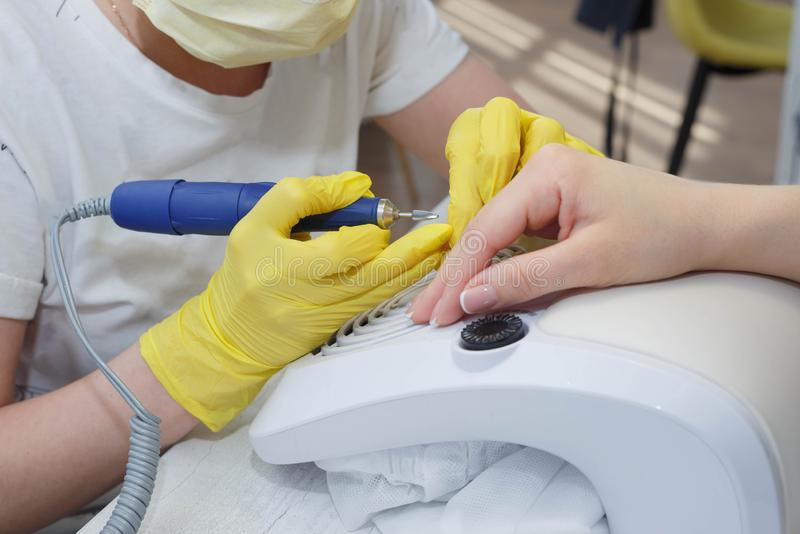 Alignment of nails as well as processing using an electric machine. The girl in the salon nail service. Alignment of nails and treatment of nails with an stock photo