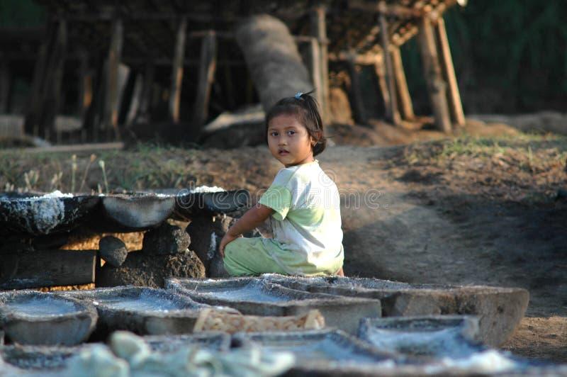 Girl in salt farm, bali, Indonesia. BALI, INDONESIA - Sep 09, 2007: small girl in salt farm, bali, Indonesia sunlit stock photography
