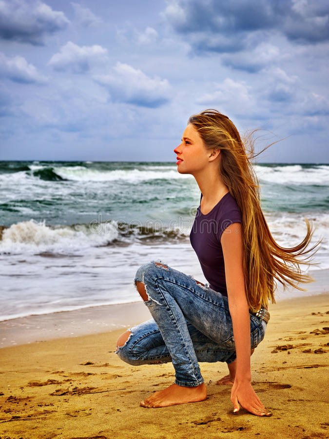 Girl on in sand beach looks thoughtfully into distance to last ray of sunset. stock photo