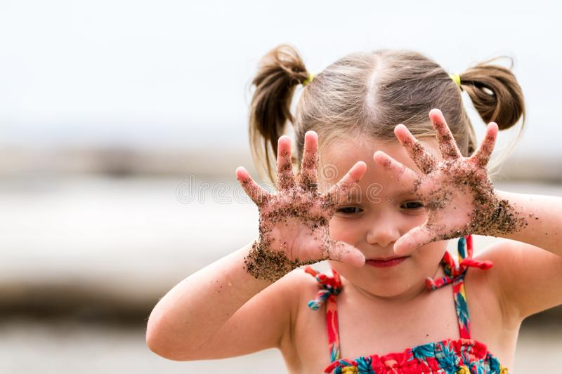 Girl with sand on her hands stock image
