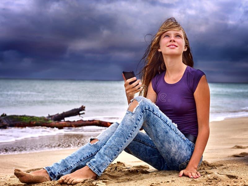 Girl on sand near sea call help by phone stock photos