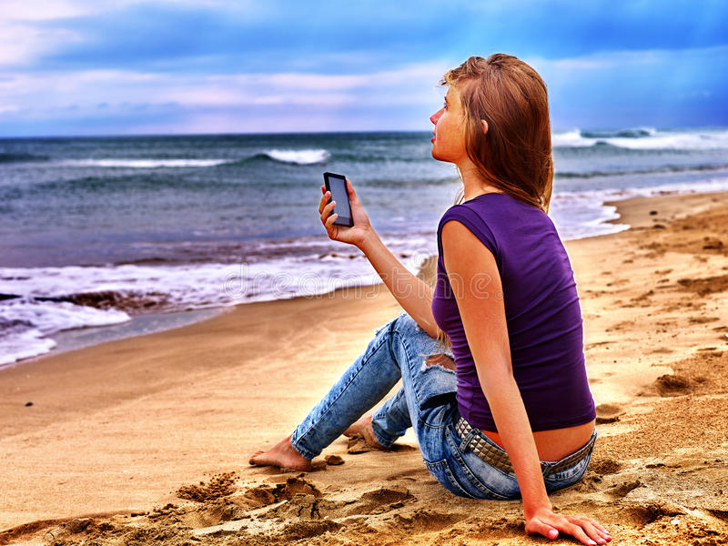 Girl on sand near sea call help by phone. stock images