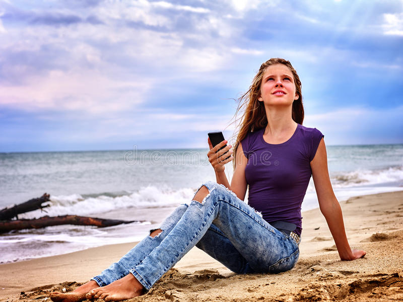 Girl on sand near sea call help by phone. stock photography