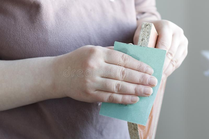 . girl with sandpaper polishes chipboard, plywood. close-up. Girl with sandpaper polishes chipboard, plywood. close-up royalty free stock images