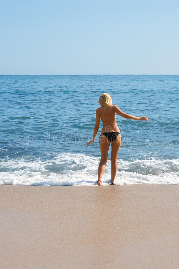 Girl on the sandy beach by the sea. Attractive girl on the sandy beach by the sea stock image
