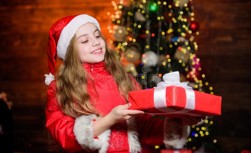 Girl santa claus costume hold christmas gift box. Prepare surprise gift. Open gift. Happy moments. Winter holidays. Christmas is time for giving. Shopping and stock photo