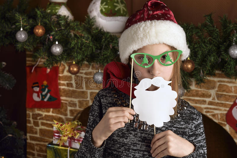 Girl in a Santa Claus costume and mask stock image