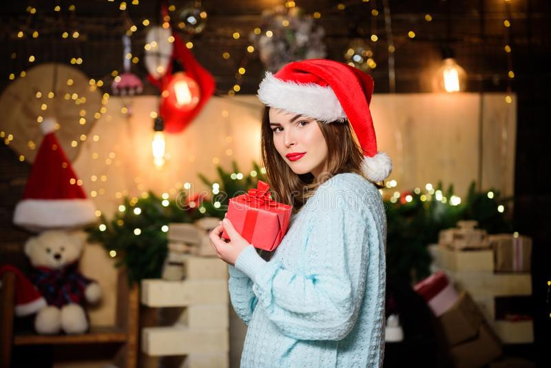 Girl in santa claus hat. Christmas shopping. Christmas tree. Winter holiday. Sexy woman with present box. Happy new year royalty free stock images