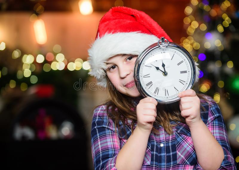 Girl santa claus hat and clock. Meet Christmas holiday. Festive atmosphere christmas day. New year countdown. Counting royalty free stock photography