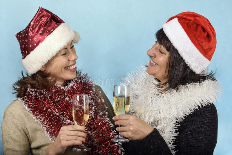 Girl in Santa Claus hats and champagne royalty free stock photos