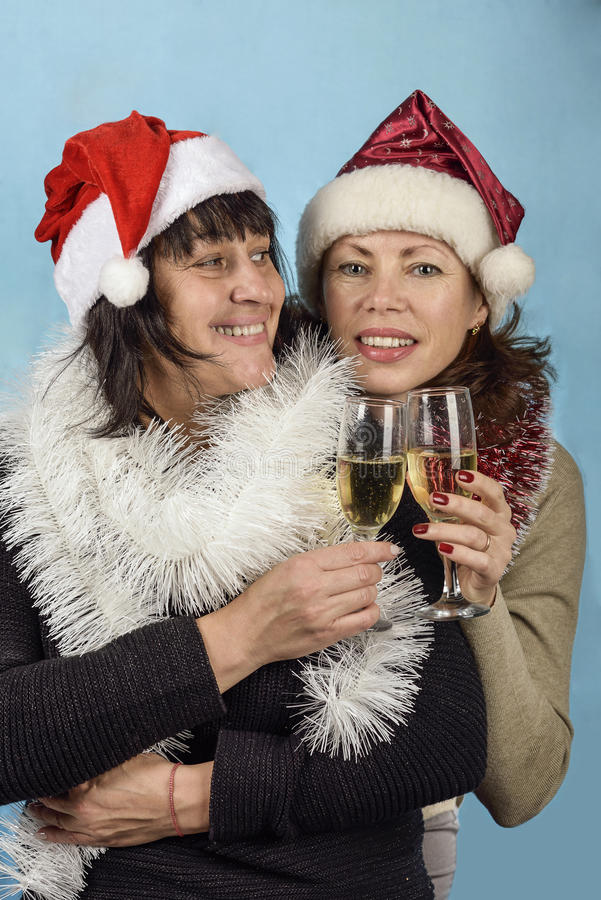 Girl in Santa Claus hats and champagne royalty free stock photo