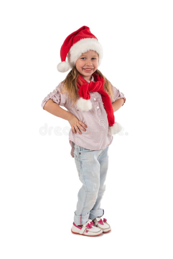 The girl in Santa Claus`s cap smiles. The child girl in Santa Claus`s cap stands and smiles royalty free stock photos