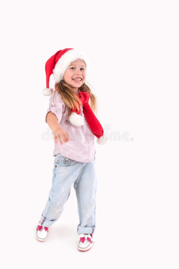 The girl in Santa Claus`s cap stands and smiles. The girl in Santa Claus`s cap stands and smiles stock photos