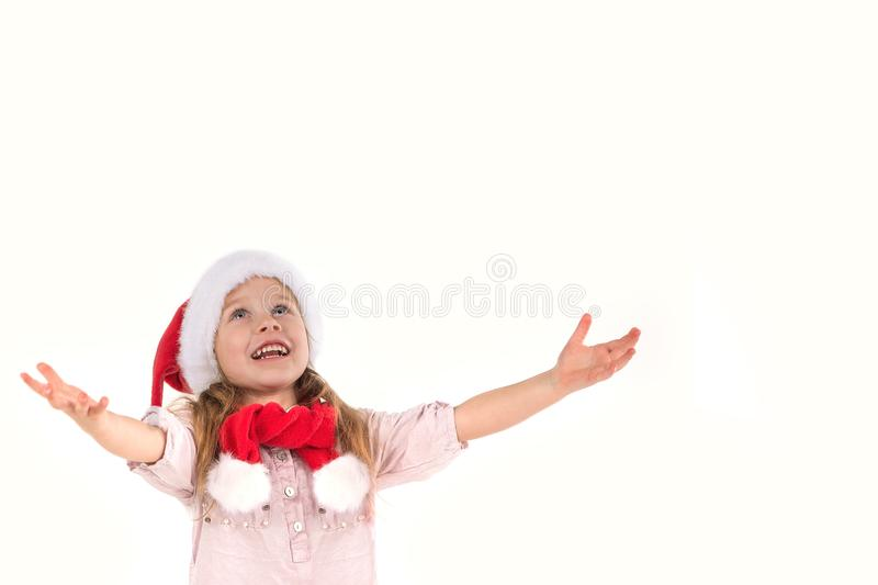 The girl in Santa Claus`s cap standss and smiles. she has raised. The girl in Santa Claus`s cap stands and smiles. she has raised hands up and rejoices stock photography
