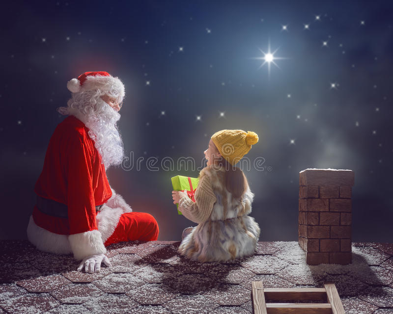 Girl and Santa Claus sitting on the roof royalty free stock images