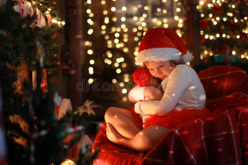 Girl in Santa hat with favorite toy doll by fireplace, Christm. Girl in Santa hat with a favorite toy doll by the fireplace on Christmas lights background stock photo